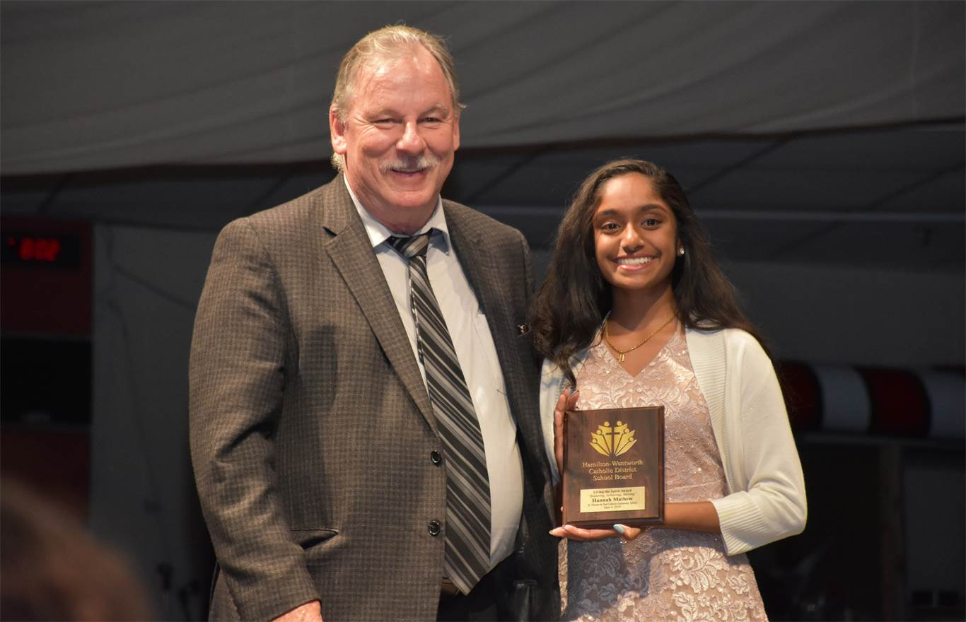 Trustee John Valvasori presents Hannah Mathew from St. Vincent de Paul with a Living the Spirit Award. The award is presented to a graduating student from each elementary and secondary school who exemplifies the qualities of the Board's logo, 'Believing, Achieving, Serving.'
