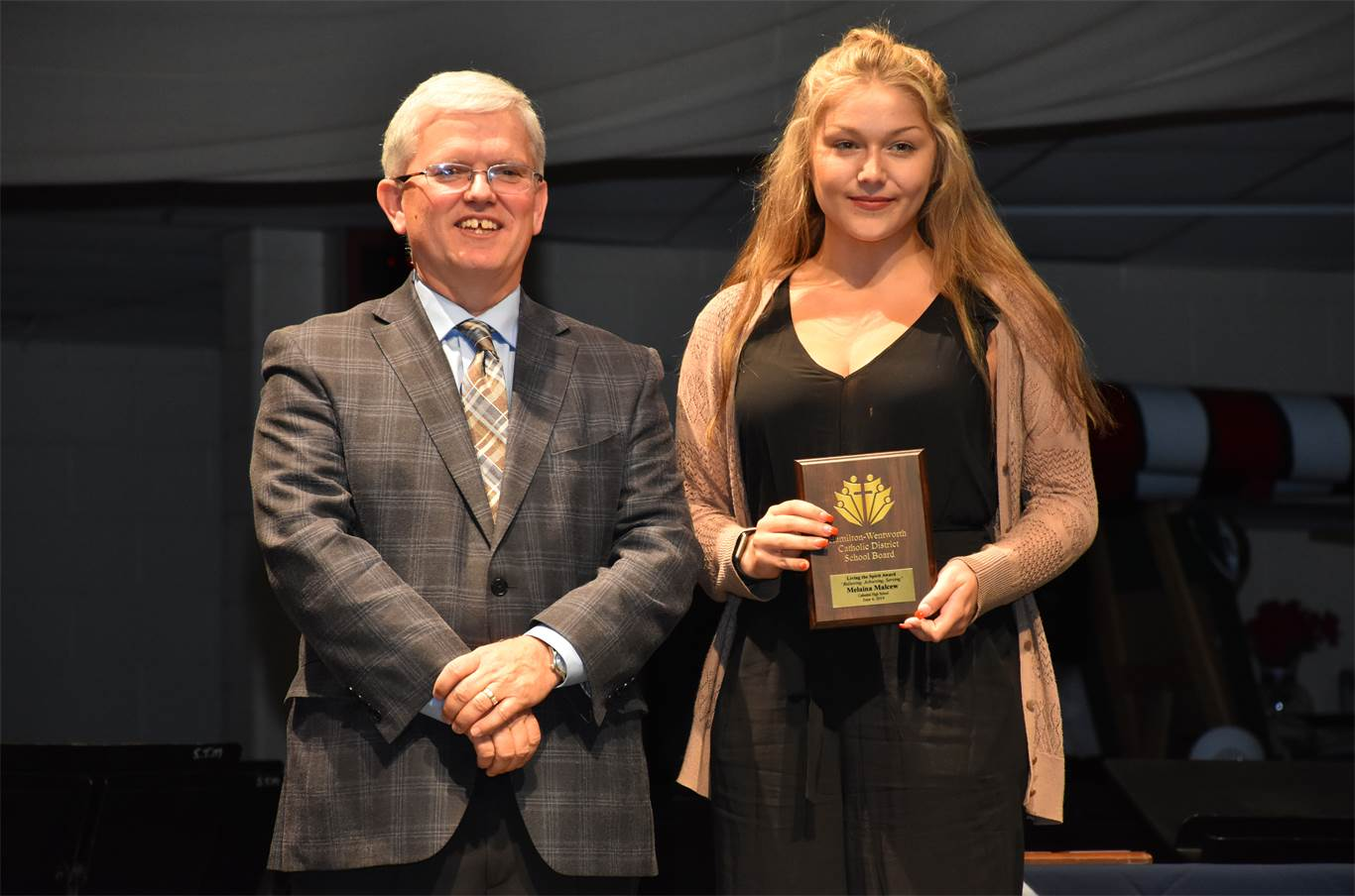 Trustee Patrick Daly presents Melaina Malcew from Cathedral High School with a Living the Spirit Award. The award is presented to a graduating student from each elementary and secondary school who exemplifies the qualities of the Board's logo, 'Believing, Achieving, Serving.'